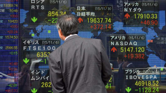A pedestrian looks at a share prices board in Tokyo, Japan.