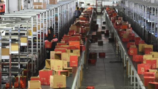 Workers sort out goods bought by customers online at a deliver center in Hangzhou on Nov. 9, 2015