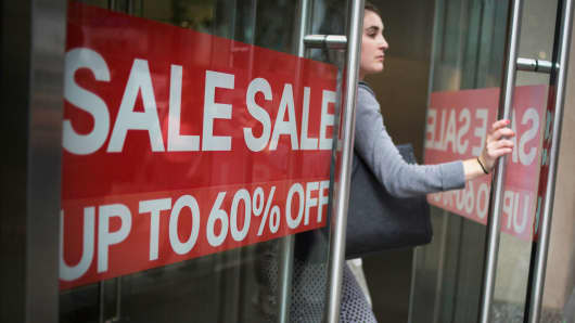 Sale signs are displayed as a shopper exits a store on 34th Street in New York.