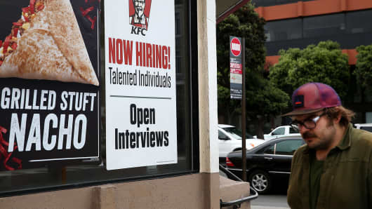 A pedestrian walks by a 'now hiring' sign at a KFC restaurant in San Francisco.