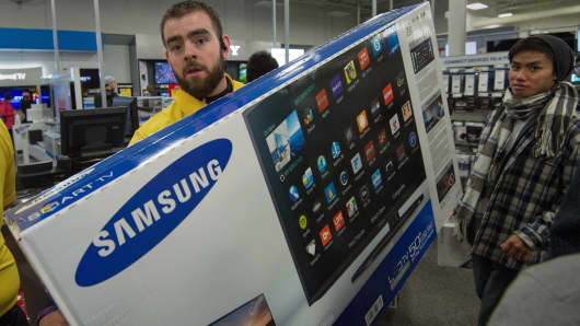 A Best Buy salesman helps a customer (R) carry his new 50' Samsung TV.