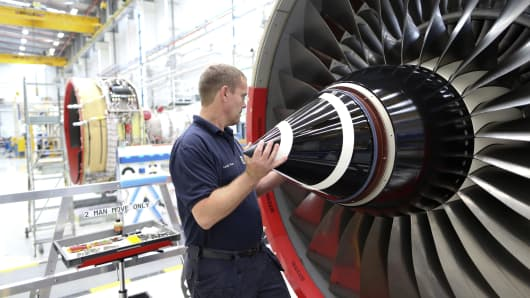 An employee fits the nose cone to a Trent 700 aircraft engine on the production line at the Rolls-Royce Holdings Plc factory in Derby, U.K.,