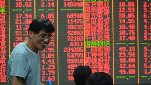 Investors observe stock market at a stock exchange hall in Hangzhou, China.