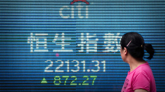 A woman walks past an electronic board displaying the benchmark Hang Seng Index in Hong Kong.