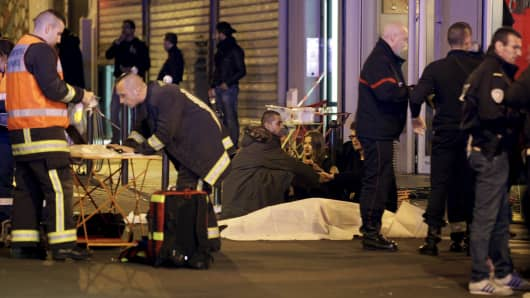Rescue services personnel working near the covered bodies outside a restaurant following a shooting incident in Paris, France, November 13, 2015.