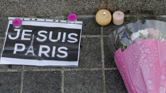 "Candles, flowers and a leaflet with the slogan ""I am Paris"" are left in tribute to victims of Paris attacks in central Strasbourg, France, November 14, 2015."
