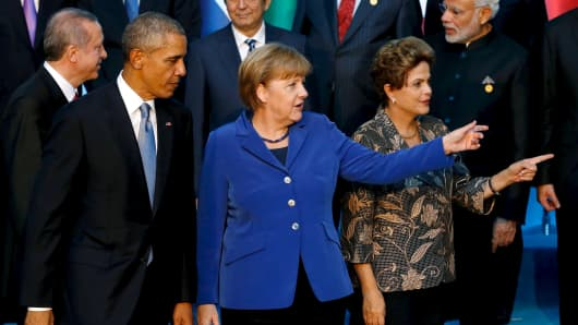 President Barack Obama (L-R) departs with Germany's Chancellor Angela Merkel and Brazil's President Dilma Rousseff after participating in a family photo with fellow world leaders at the start of the G20 summit at the Regnum Carya Resort in Antalya, Turkey, November 15, 2015.