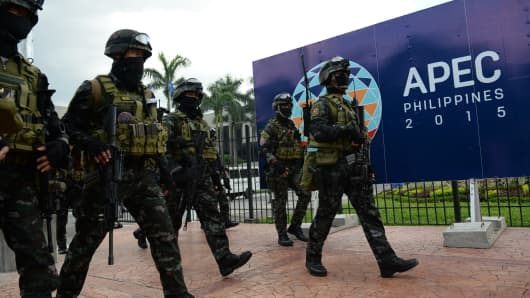 Members of the police Special Action Force (SAF) walk in front of signage for the Asia-Pacific Economic Cooperation (APEC) summit after a drill simulating a Paris-like attack at the venue of the summit in Manila on November 14, 2015.