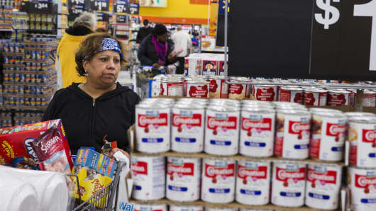 A shopper inspects cans of evaporated milk at a Walmart store in Secaucus, New Jersey.
