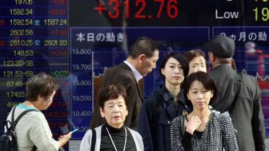 Pedestrians walk past a share prices board in Tokyo on November 17, 2015.