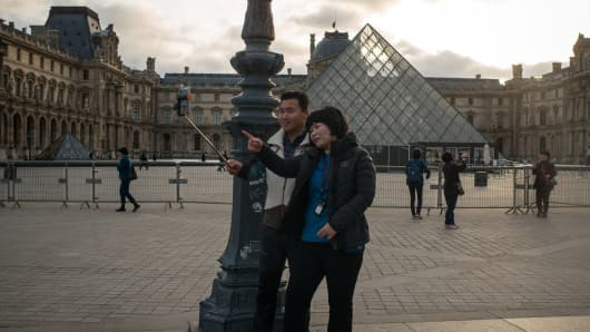 Korean tourists pose for a selfie outside the Louvre musem on Nov. 15, 2015 in Paris.