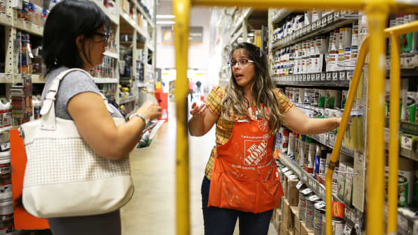 A Home Depot employee helps a customer as she shops in the paint department at the store in Miami, Florida.