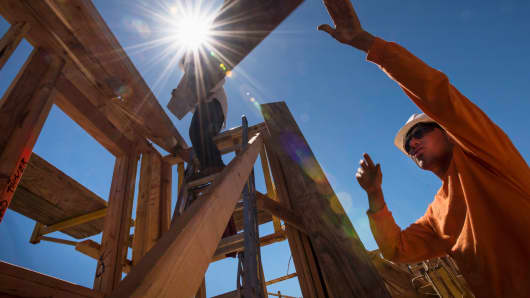 Workers load wood planks on a house under construction in Livermore, California.
