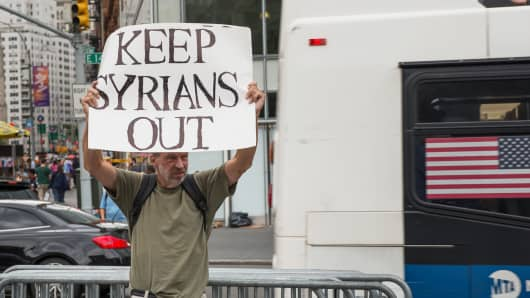 An anti-Syrian refugee protester stands on the streets of New York City.