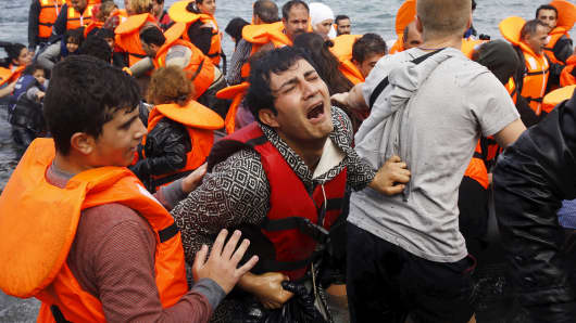 A Syrian refugee cries while disembarking from a flooded raft at a beach on the Greek island of Lesbos.