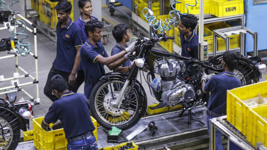 Employees assemble a Royal Enfield Motors Classic 350 motorcycle moving on a conveyor on the production line at the company's manufacturing facility in Chennai, India.