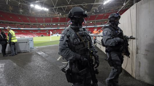 Two British Counter Terrorist Specialist Firearms Officers (CTSFO) carry their guns as they patrol inside Wembley Stadium ahead of the friendly football match between England and France at Wembley Stadium in west London on November 17, 2015.