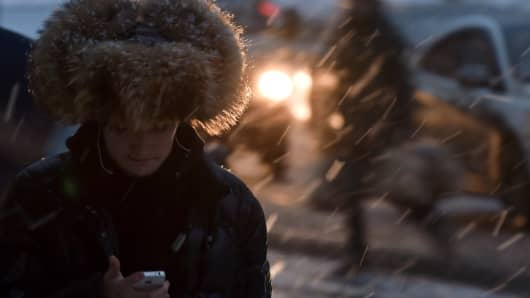A man walks along a street in central Moscow during a snowfall.