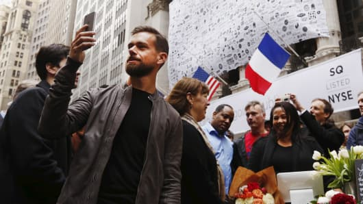 Jack Dorsey (L), CEO of Square and CEO of Twitter, live casts video while standing outside the New York Stock Exchange for the IPO of Square, in New York November 19, 2015.