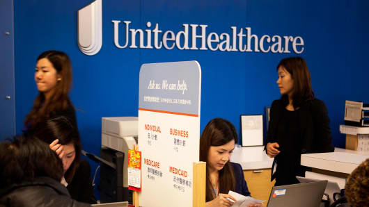 Representatives speak with customers at a UnitedHealthcare store in Queens, New York.