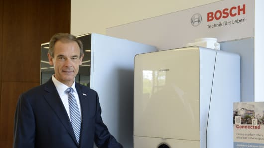 Volkmar Denner, CEO of German technology company Robert Bosch GmbH, poses next to a condensate boiler which can be operated with a smartphone during the company's annual press conference at the Bosch headquarters in Gerlingen near Stuttgart, southwestern Germany