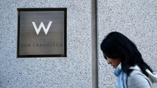 A pedestrian walks by a W hotel in San Francisco.