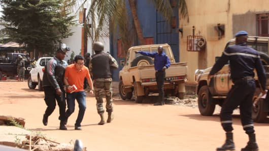 A Mali trooper, left, assist a hostage, second left, to leave the scene, from the Radisson Blu hotel to safety after gunmen attacked the hotel in Bamako, Mali, Friday, Nov. 20, 2015.