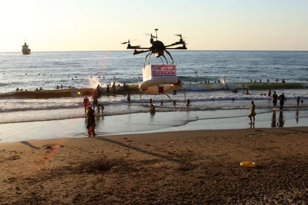 A drone, called 'The Guardian', carrying a life preserver and flying above people at a public beach as it is tested to save swimmers in peril in Lebanon's southern port city of Sidon.