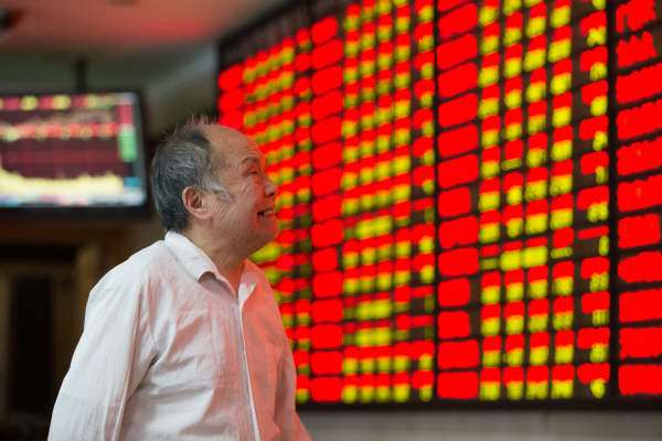 An investor observes stock market at a stock exchange hall in Nanjing, Jiangsu province, China.