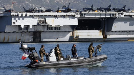 French army soldiers secure the area around the nuclear-powered aircraft carrier Charles de Gaulle as it leaves the naval base of Toulon, France, November 18, 2015.