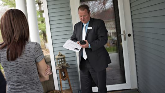 A real estate agent with a potential homebuyer outside a home in Mackinaw, Ill.