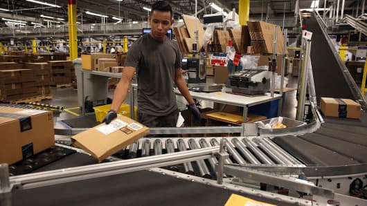 An Amazon.com worker sorts packages onto a conveyor belt at an Amazon fulfillment center in Tracy, California.
