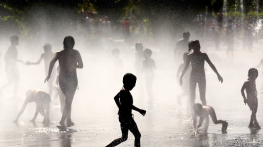 Children cool off as they play under a fountain July 21, 2015 in Madrid, Spain.