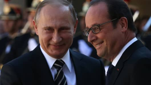 Russian President Vladimir Putin (L) is greeted by French President Francois Hollande (R) prior to their meeting at the Elysee Presidential Palace on October 2, 2015 in Paris, France.