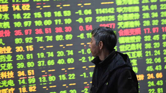 A investor observes stock prices at an exchange hall in Hangzhou, China.