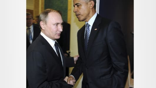 Russian President Vladimir Putin (L) shakes hands with President Barack Obama as they meet during the World Climate Change Conference 2015 at Le Bourget, France, November 30, 2015.