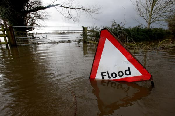 A flood sign is seen in flood waters surrounding farm buildings on January 28, 2014 in Somerset, England.