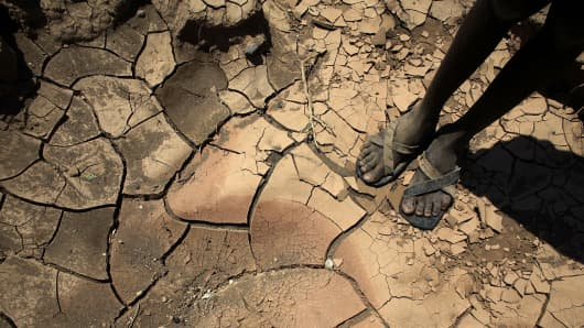 A young boy from the remote Turkana tribe in Northern Kenya stands on a dried up river bed near Lodwar, Kenya.