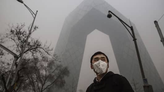 A Chinese man wears a protective face mask as he passes by the CCTV Headquarters on November 30, 2015, in Beijing, China.