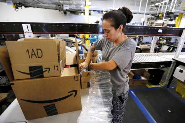 An employee secures customers' orders with bubble wrap before they are shipped at the Amazon Fulfillment Center in Tracy, Calif.