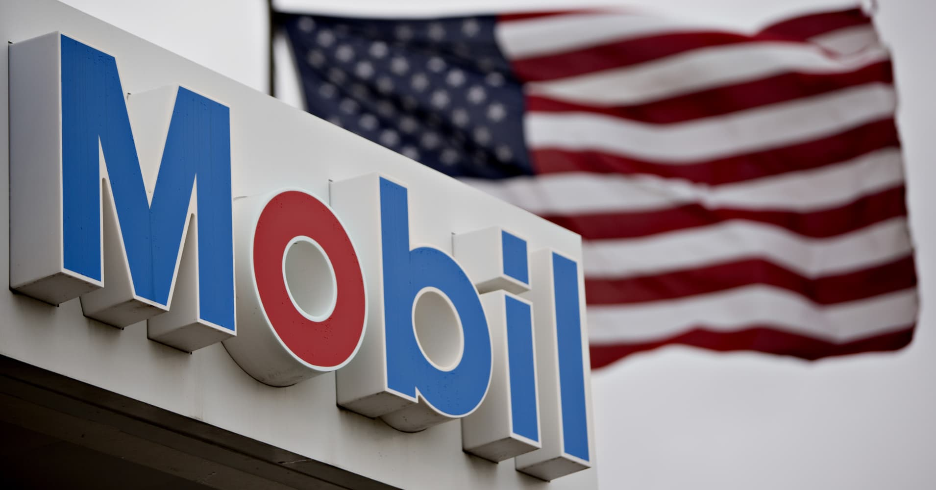 Exxon mobil to invest 35 billion in us over 5 years citing tax cuts an american flag flies next to signage at an exxon mobil corp gas station in buycottarizona