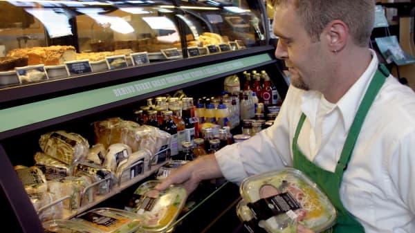 A Starbucks employee organizes salads and sandwiches.