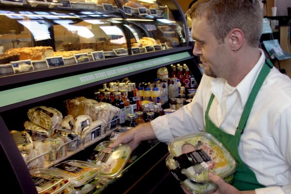 A Starbucks employee organizes salads and sandwiches.