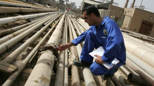 An Iraqi worker gauges gas emissions from an oil pipe at the Daura oil refiner