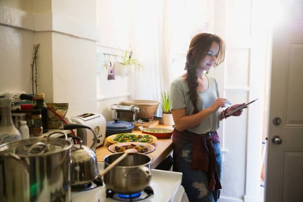 Woman cooking in kitchen with tablet