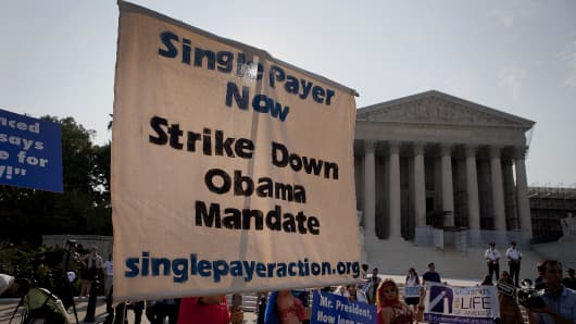 Members of the Single Payer Action group opposed to the Affordable Care Act hold a sign outside the Supreme Court building in Washington, D.C.
