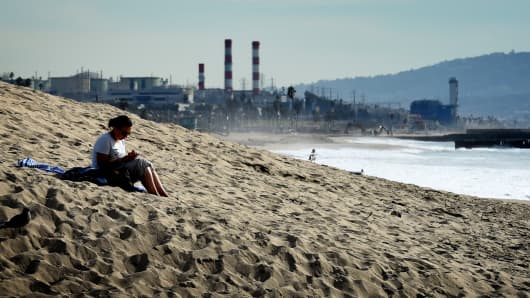A woman sits on a sand berm created by city workers to protect houses from El Nino storms and high tides at Playa Del Rey beach in Los Angeles, on November 30, 2015.