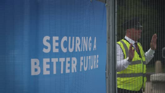 A G4S private security guard stands at the perimeter fence of the International Convention Center ahead of the Conservative party conference in Birmingham, England.