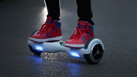 A youth poses as he rides a hoverboard, which are also known as self-balancing scooters and balance boards.