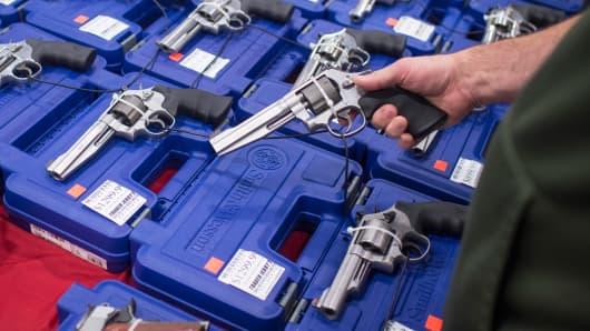 People look at handguns at The Nation's Gun Show in Chantilly, VA.